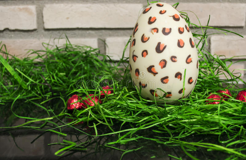 Chocolate white Easter egg with red bonbons and green 3 royalty free stock photo