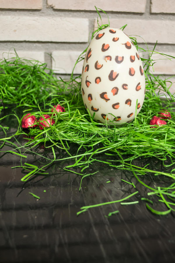 Chocolate white Easter egg with red bonbons and green 4 royalty free stock photos