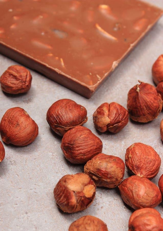 Chocolate y avellanas nutritivos en la estructura del cemento foto de archivo libre de regalías
