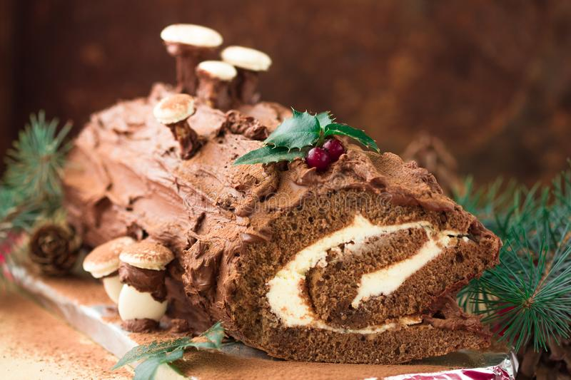 Chocolate yule log christmas cake with red currant on wooden background. Christmas chocolate yule log with decor of colored chocol royalty free stock image