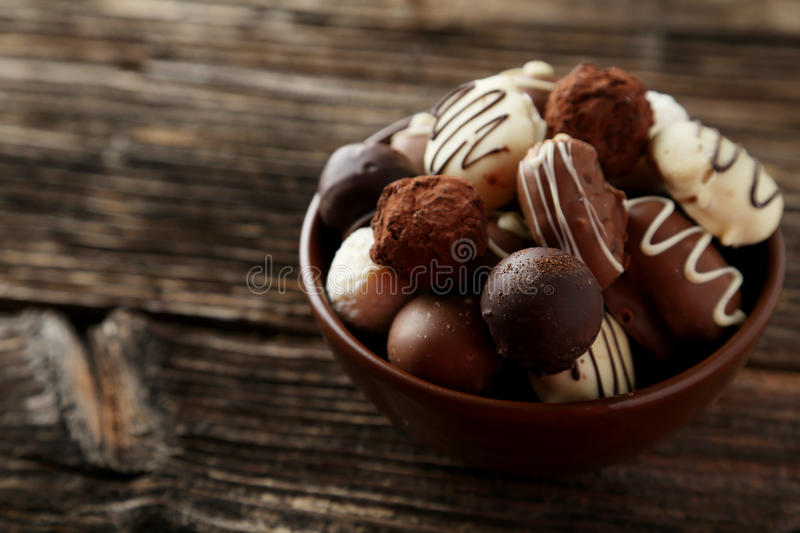 Chocolates in bowl on the brown wooden background royalty free stock photo