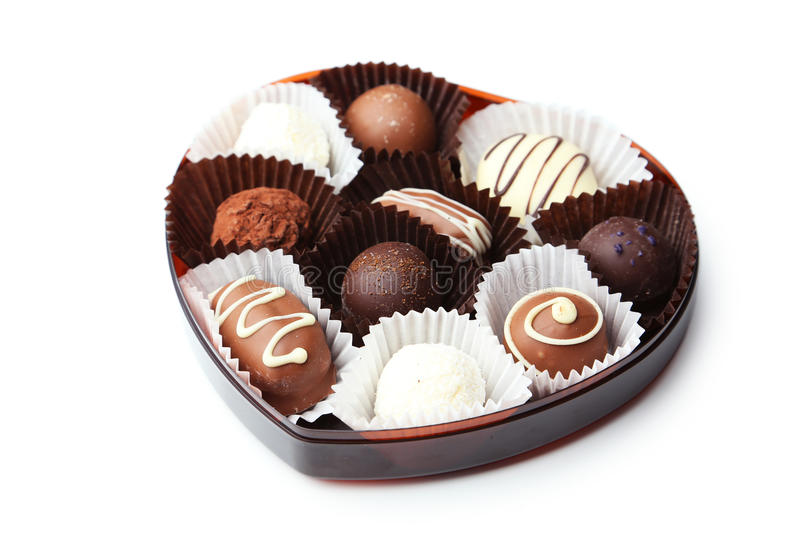 Chocolates in bowl on the white wooden background royalty free stock photo