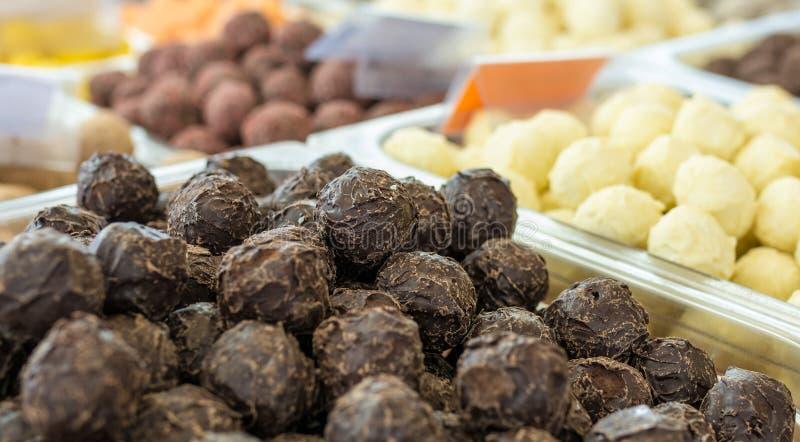 Chocolates deliciosos das trufas com cacau no primeiro plano em um mercado do chocolate imagens de stock royalty free