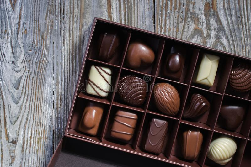 Chocolates in different shapes and colors in gift box on wooden table. Flat lay. stock photos