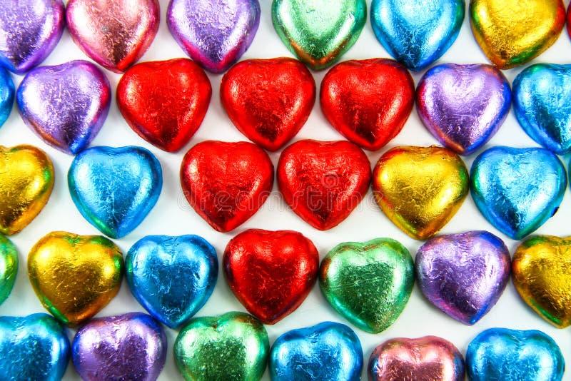 Chocolates do coração envolvidos na folha colorida imagem de stock royalty free
