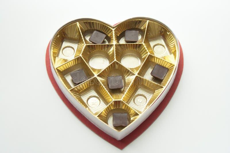 Chocolates en una lata y una caja en forma de corazón fotos de archivo libres de regalías