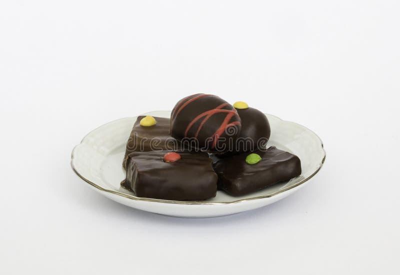 Chocolates en una placa contra el fondo blanco fotografía de archivo libre de regalías