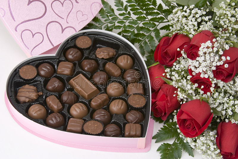 Chocolates n Roses. Picture of a dozen Red Roses on white background with Heart Shaped Box of Chocolates