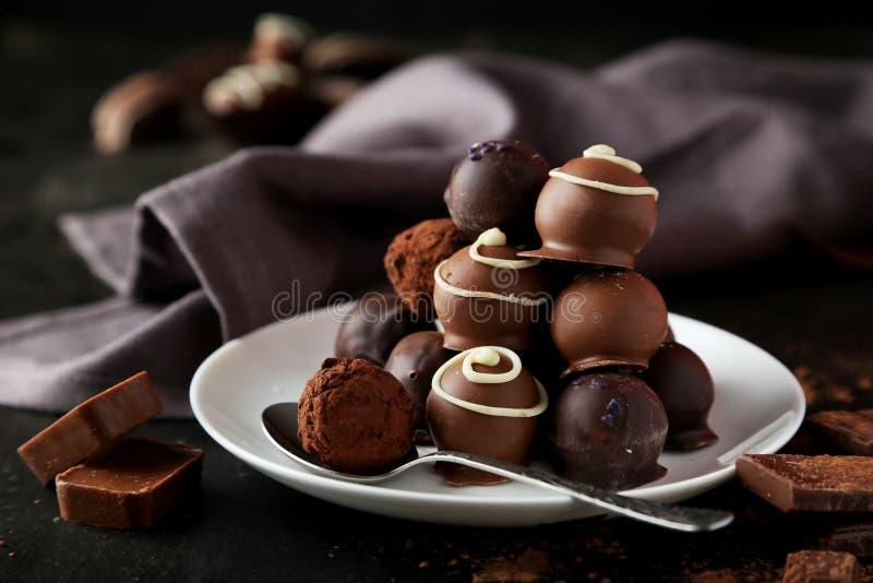 Chocolates na placa no fundo preto fotos de stock