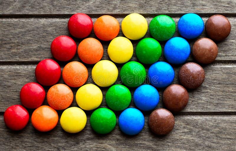 Chocolates no esmalte empilhado na bandeira de LGBT no fundo de madeira fotografia de stock royalty free