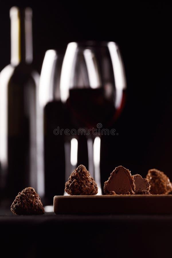 Chocolates, vinho com o vidro no fundo preto no borrão imagens de stock royalty free