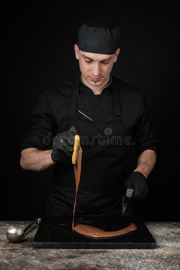 Chocolatier in black uniform in the process of making chocolates. Making sweets. Photo in studio, on a black background royalty free stock image
