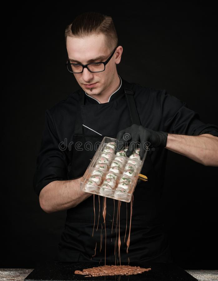 Chocolatier in black uniform in the process of making chocolates. Making sweets. Photo in studio, on a black background royalty free stock images
