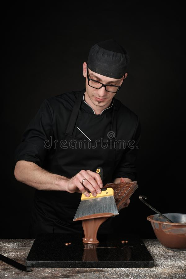 Chocolatier in black uniform in the process of making chocolates. Making sweets. Photo in studio, on a black background royalty free stock photos