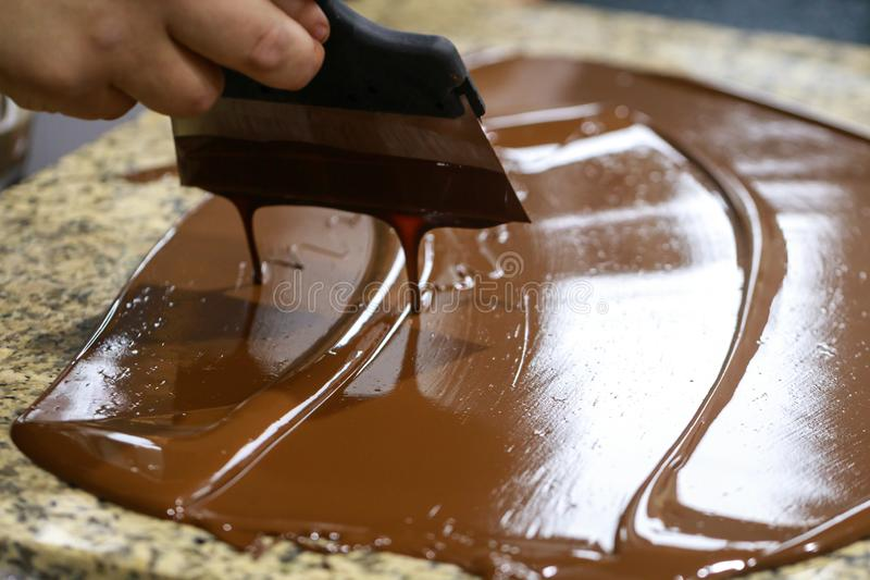 Chocolatier with a spatula is stirring the tempered liquid chocolate on a granite table.  stock photography