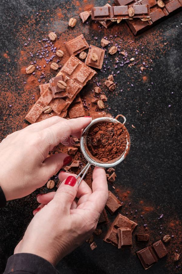 Chocolatier sprinkles pieces of chocolate cocoa powder.  stock photography
