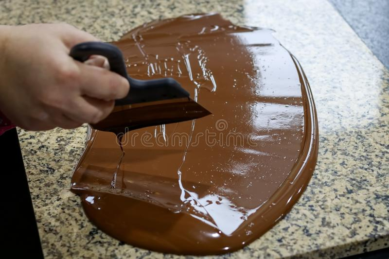 Chocolatier stirs the tempered chocolate on a granite table in order to cool.  royalty free stock photo