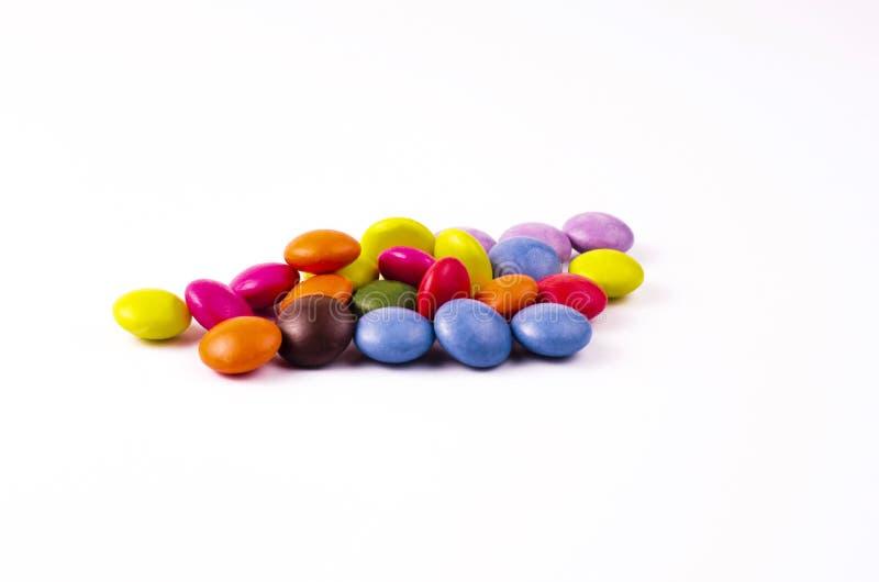 Chocolats avec un revêtement multicolore sur un fond blanc photo stock