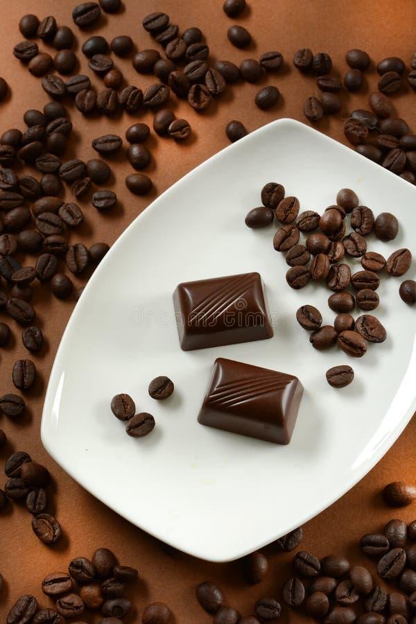 Chocolats de café avec des grains de café à côté de lui photographie stock