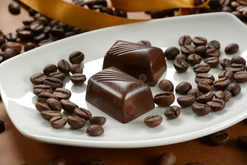 Chocolats de café avec des grains de café à côté de lui photographie stock libre de droits