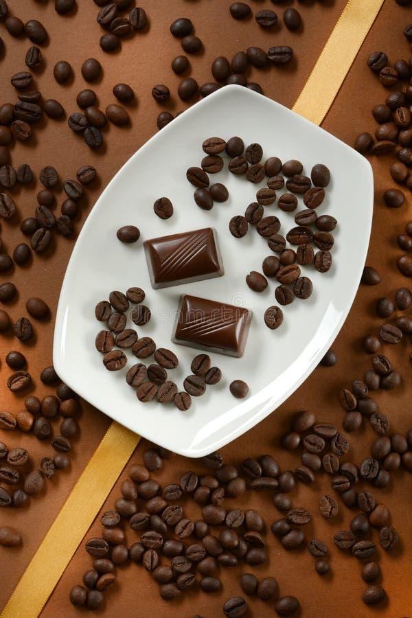 Chocolats de café avec des grains de café à côté de lui image libre de droits