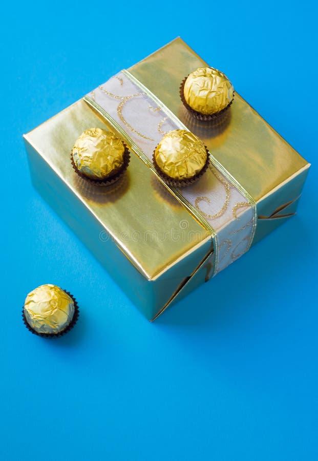 Chocolats enveloppés placés sur le boîte-cadeau d'or images stock