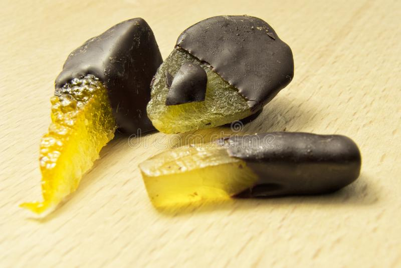 Chocolats foncés de chocolat avec la poire, l'orange et le gingembre sur un hachoir en bois photo stock