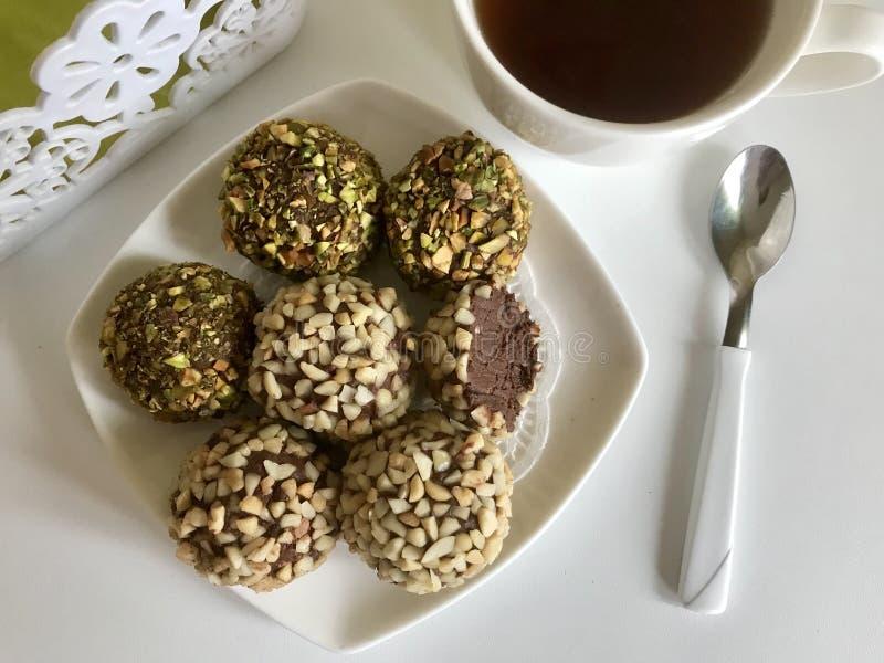 Chocolats sous forme de boules couvertes d'arachides et de pistaches coupées Est tout pr?s une tasse de caf? photos libres de droits