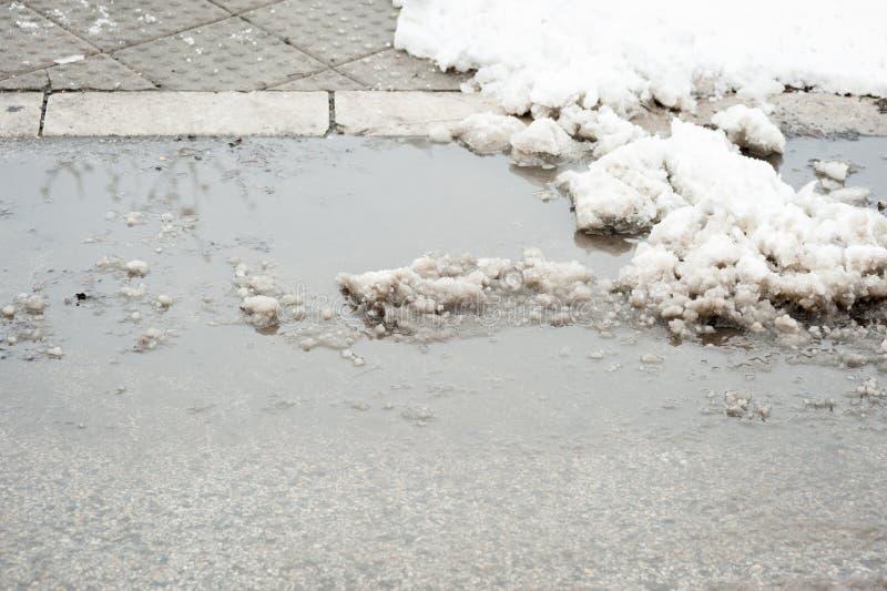 Chodniczek z crosswalk zakrywającym z rozciekłym śniegiem i wodną garnek dziurą w zimie obrazy stock