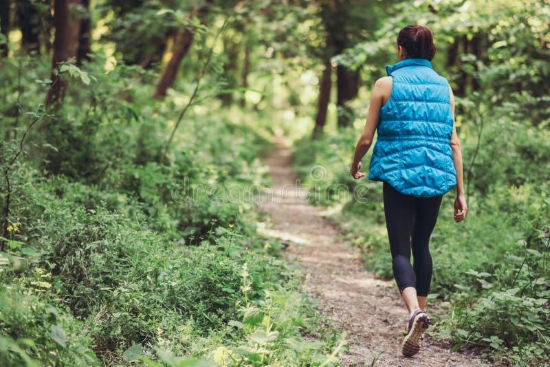 Chodząca młoda sporty kobieta w błękit ciepłej sleeveless kurtce na naturze, park, lasowy tło fotografia stock