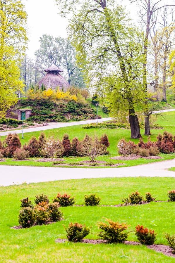 Chodząca ścieżka w parku otaczającym różnorodnymi roślinami i lasowym buda dachem robić cienkie gałąź na tle zdjęcia stock