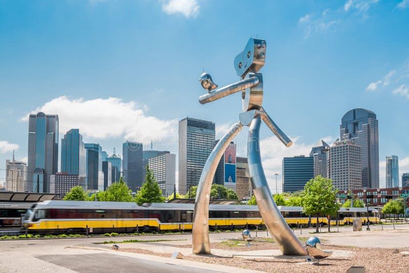 Chodząca mężczyzna statua Dallas Teksas z linią horyzontu i pociągiem zdjęcia royalty free