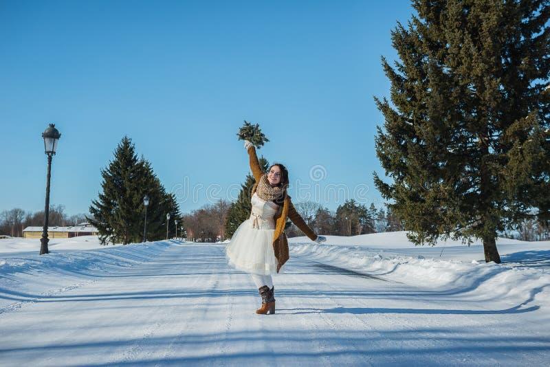 Chodząca panna młoda na śnieżnej drodze piękna brunetka w ślubnej sukni, wieśniaka stylu z chojaka ślubnym bukietem krótkich, i zdjęcia stock