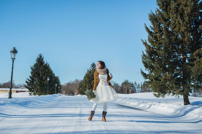 Chodząca panna młoda na śnieżnej drodze piękna brunetka w ślubnej sukni, wieśniaka stylu z chojaka ślubnym bukietem krótkich, i fotografia royalty free