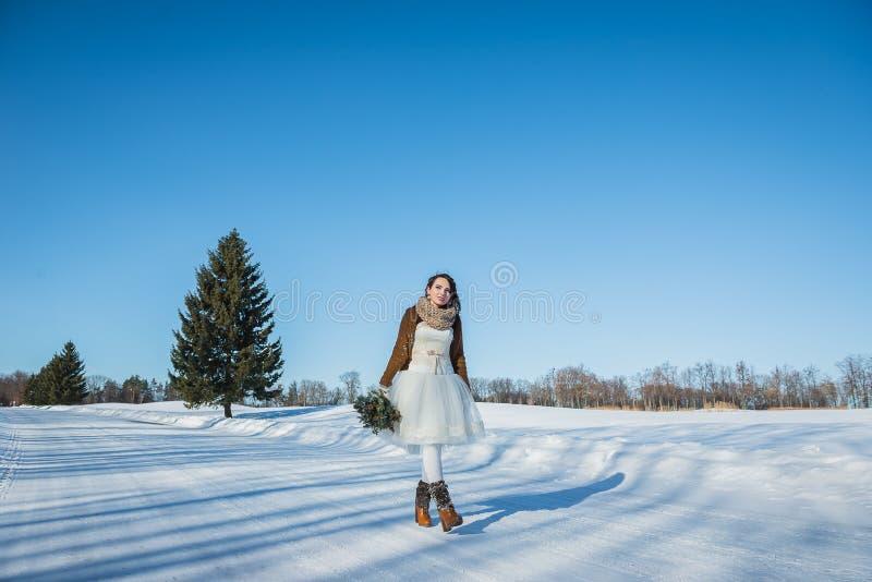 Chodząca panna młoda na śnieżnej drodze piękna brunetka w ślubnej sukni, wieśniaka stylu z chojaka ślubnym bukietem krótkich, i zdjęcia royalty free