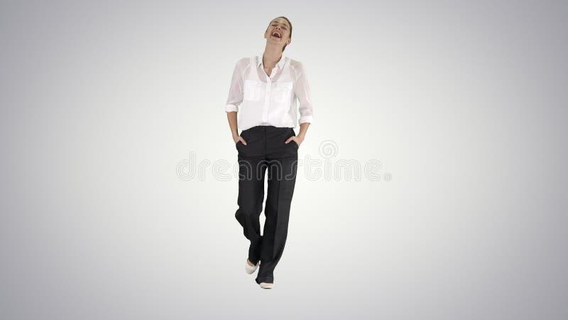 Chodzący bizneswoman z rękami w kieszeniach i śmiać się na gradientowym tle zdjęcie stock