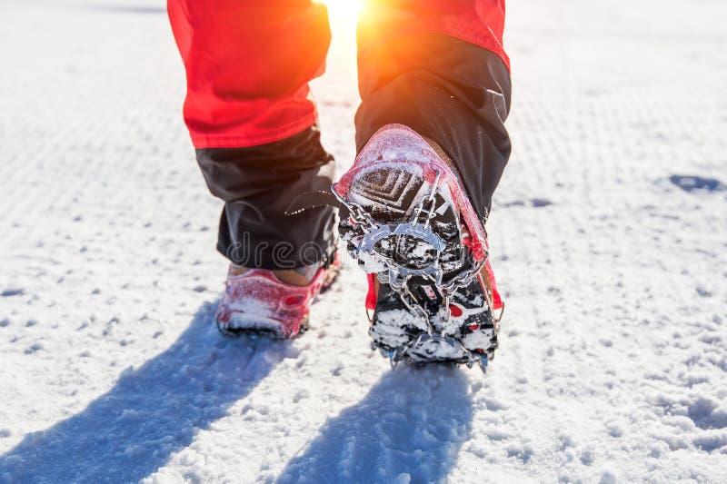 Chodzić na śniegu z Śnieżnymi butami i butów kolcami w zimie zdjęcie stock