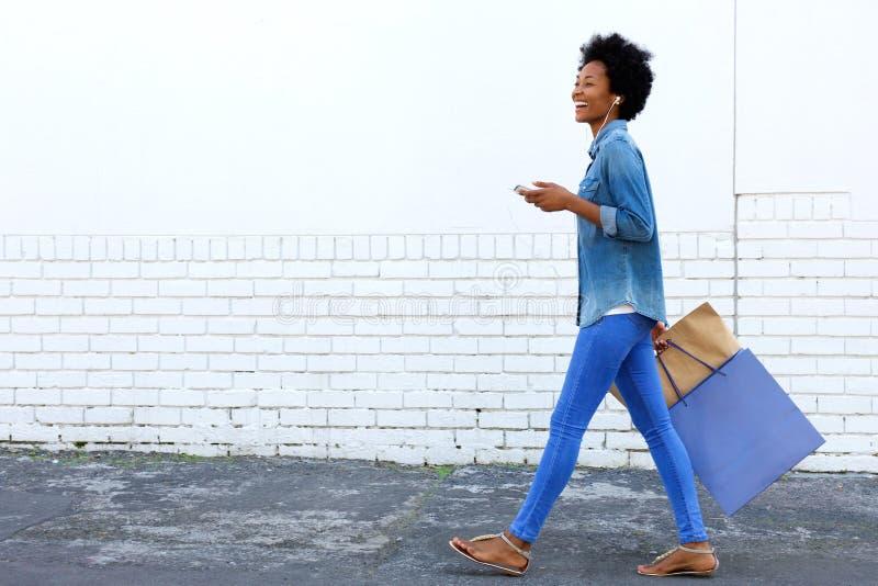 Chodzić z torba na zakupy i słuchanie muzyka fotografia stock
