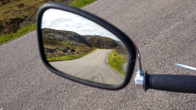 Chodziło o zamazane lusterko motocyklowe z drogą odbicia gdzieś w Szkocji fotografia stock