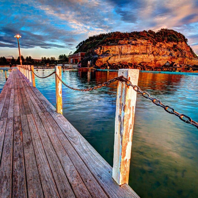 Chodzi sposób i prowadzi łańcuch wzdłuż strony th oceanu basen w wczesnym poranku 1x1 zdjęcia stock