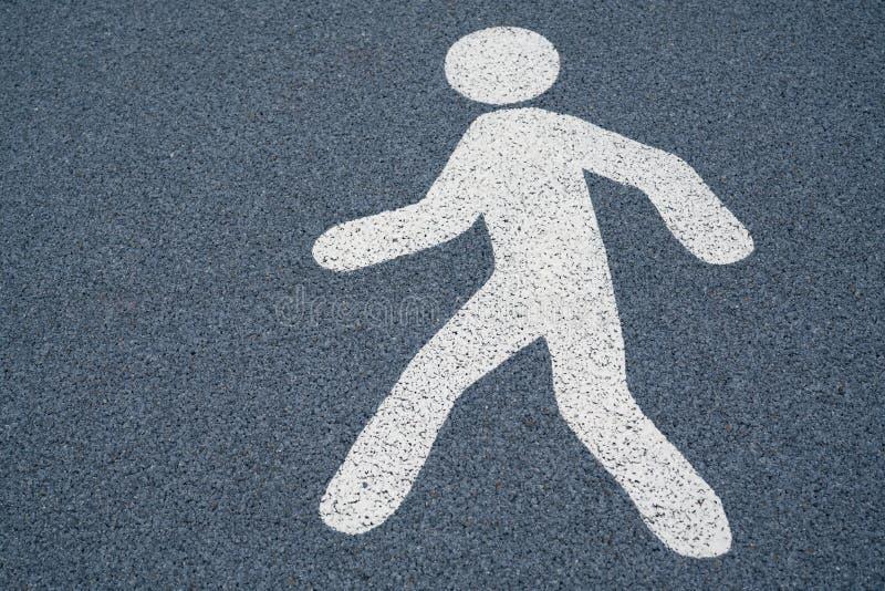 Chodzi szyldowego, zwyczajnego znaka ulicznego na mokrej zmroku asfaltu podłoga, obraz stock