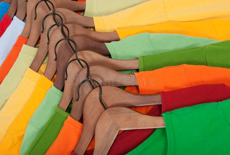 Choice Of Colorful T-shirts On Wooden Hangers Stock Images