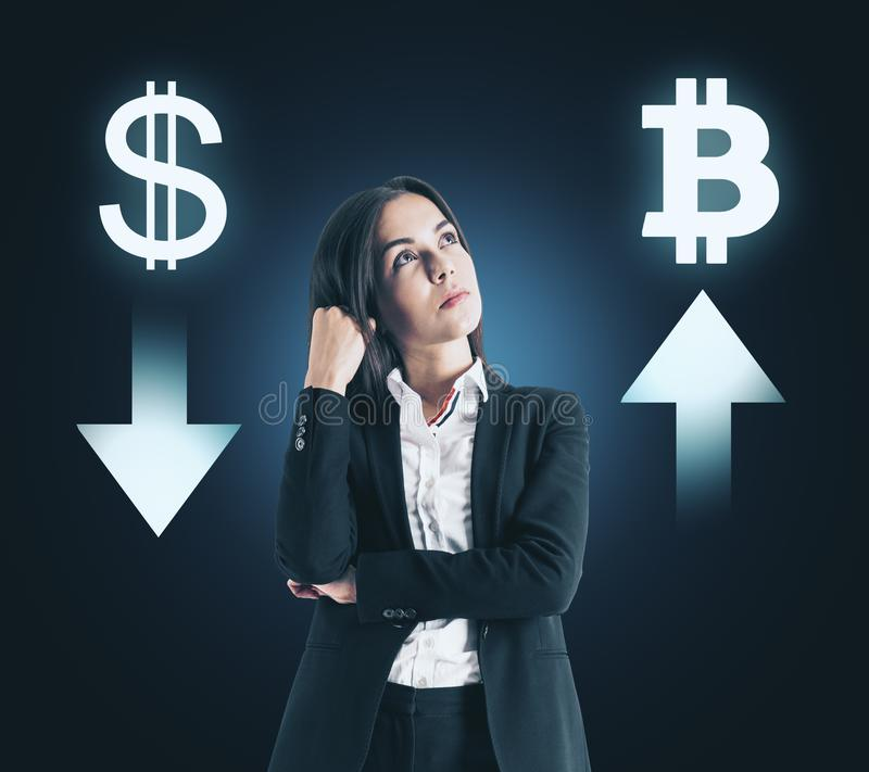 Choice, cryptocurrency and bitcoin concept. Portrait of attractive thoughtful young businesswoman with digital money signs on dark background stock images