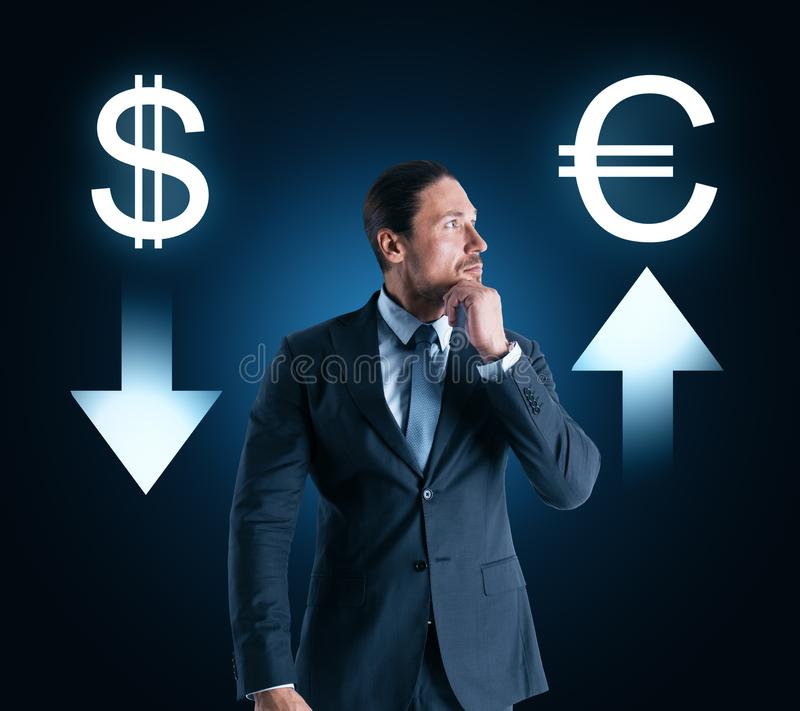 Choice, cryptocurrency and stock concept. Portrait of attractive thoughtful young businessman with digital money signs on dark background royalty free stock image