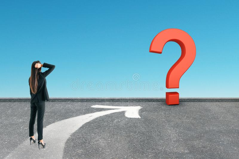 Choice and doubt concept. Back view of young businesswoman standing on road with arrow and question mark. Sky background. Choice and doubt concept royalty free stock photography