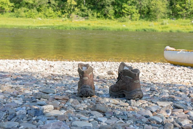The choice of shoes for tourism and trekking. Brown boots stand on a stony bank. stock image