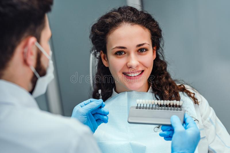 Choice of tooth color with a special scale. Dentist select a shade of tooth enamel for the young pretty girl of the patient. Bleaching, prosthetics, orthopedic stock photo