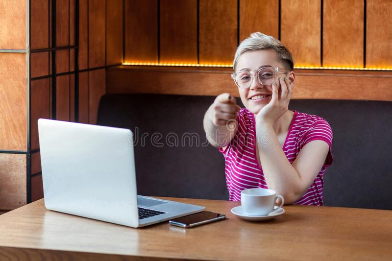 Choice you! Positive young girl freelancer with blonde short hair, in pink t-shirt and eyeglasses is sitting in cafe, working on. Laptop, pointing finger to you royalty free stock images