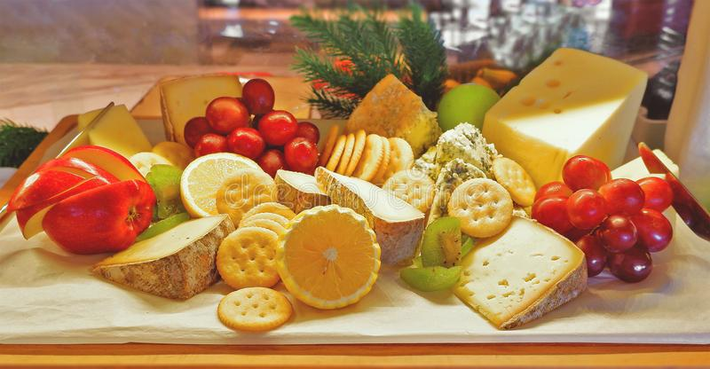 Choices of cheese variety with fruits and biscuits on a board royalty free stock photo