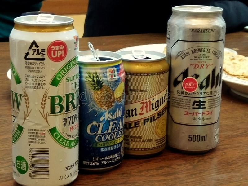 Choices of Japanese beer. Four cans of cold Japanese beers on the wooden table stock photos